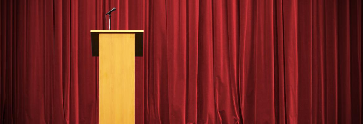 podium in front of red curtain